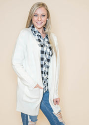 Layer your winter white cardigan with a pop of plaid underneath