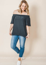 off the shoulder black blouse with pom pom details on hem