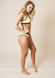yellow two piece sporty swimsuit with zipper features on the top and bottoms