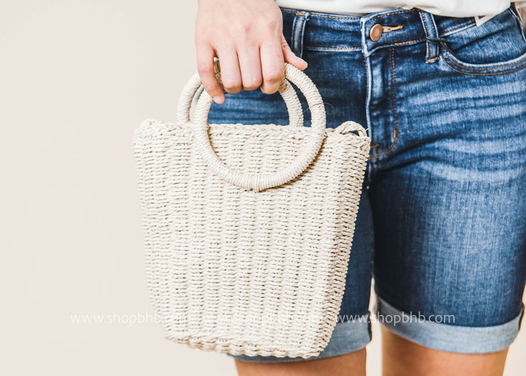 woven bamboo bag features a long braided strap and a round strap