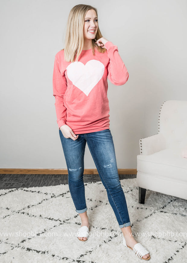 A faded red long sleeve top decorated with a large white heart for Valentines Day.