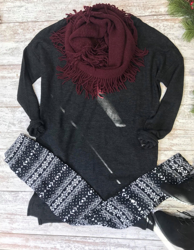 This bundle deal for the 6th day of christmas include this comfy black tunic, snowflake leggings, and a burgundy fringe scarf.