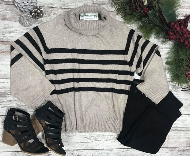 This Turtle neck oatmeal sweater in 3/4 sleeve hits right at the belt line and the cutest black stripes through out perfect for sweater weather.