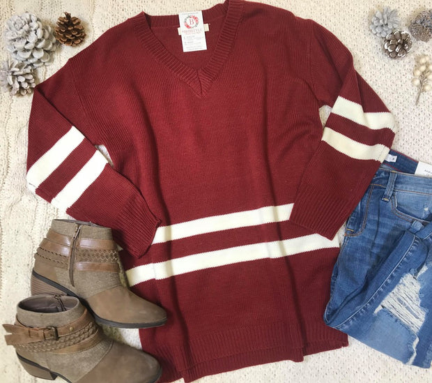 This Burgundy v-neck sweater is a varsity style with 2 ivory stripes on the sleeves and the body.