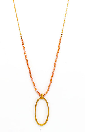 Long goldtone metal pendant with coral beads