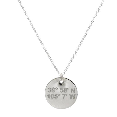 Lat & Lo disc necklace in sterling silver inscribed with custom coordinates.