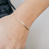 dainty coordinates bar bracelet in gold by Lat & Lo on model's wrist