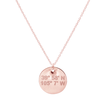 Lat & Lo disc necklace in rose gold inscribed with custom coordinates.