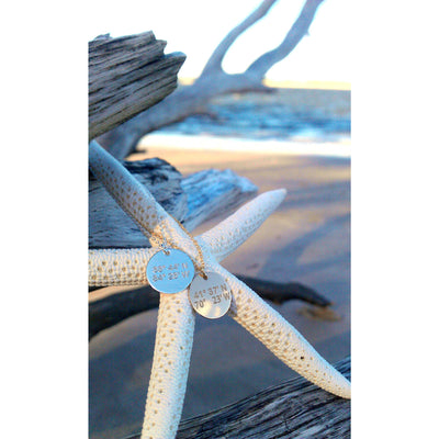 Lat & Lo disc necklace custom inscribed with coordinates hanging on a star fish on the beach.