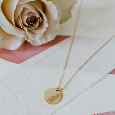 Lat & Lo disc necklace in 14K gold filled, with custom back inscription laying flat with rose.