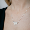 Triangle Coordinates necklace inscribed with latitude-longitude coordinates. Shown on model in sterling silver. By Lat & Lo. www.latanldo.com
