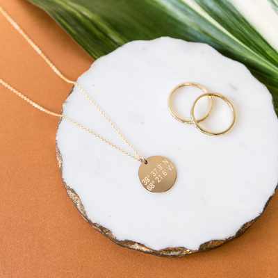 Lat & Lo disc necklace inscribed with custom coordinates picture with two Journey rings.