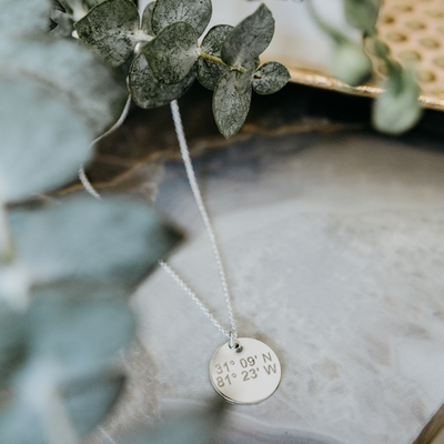 Lat & Lo Disc necklace inscribed with coordinates in sterling silver, laying flat around greenery.