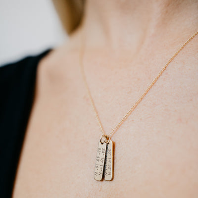 Lat & Lo coordinates charm necklace in gold with two charms on model