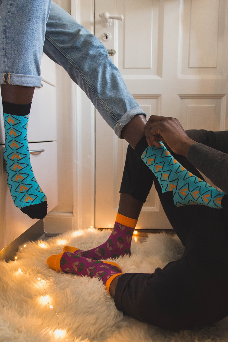 Black couple sitting on the floor dressing colorful bamboo socks