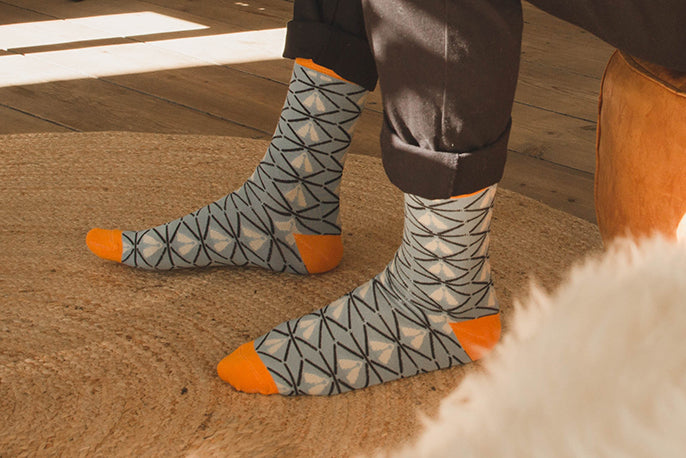 Two feet on a carpet wearing blue bamboo socks with african design