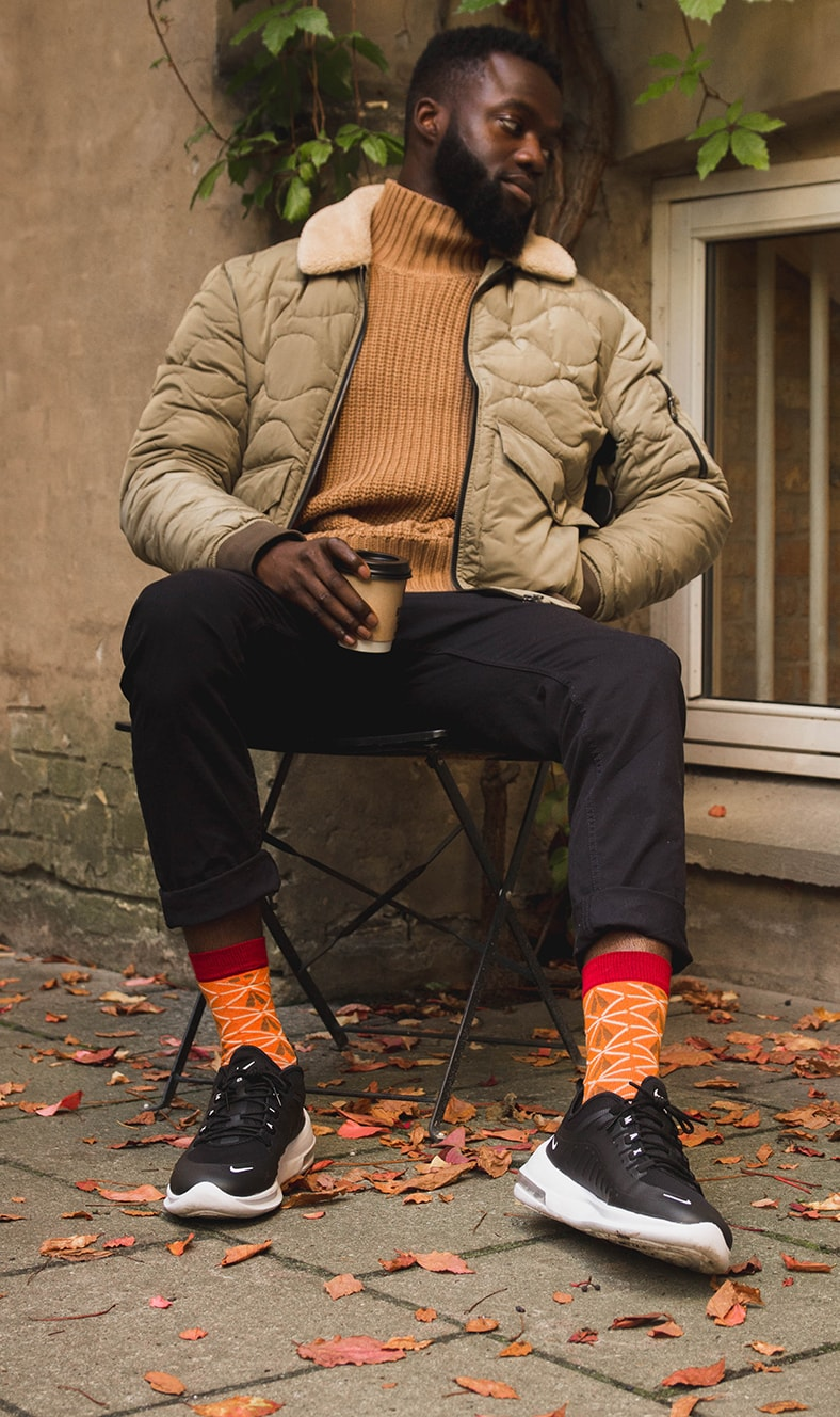 black man sitting on a chair outside with red bamboo socks with african design