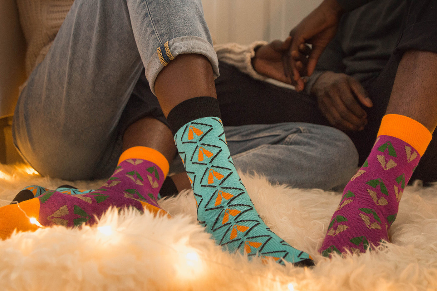 Black couple sitting on the floor holding bands wearing blue and purple bamboo socks with african design