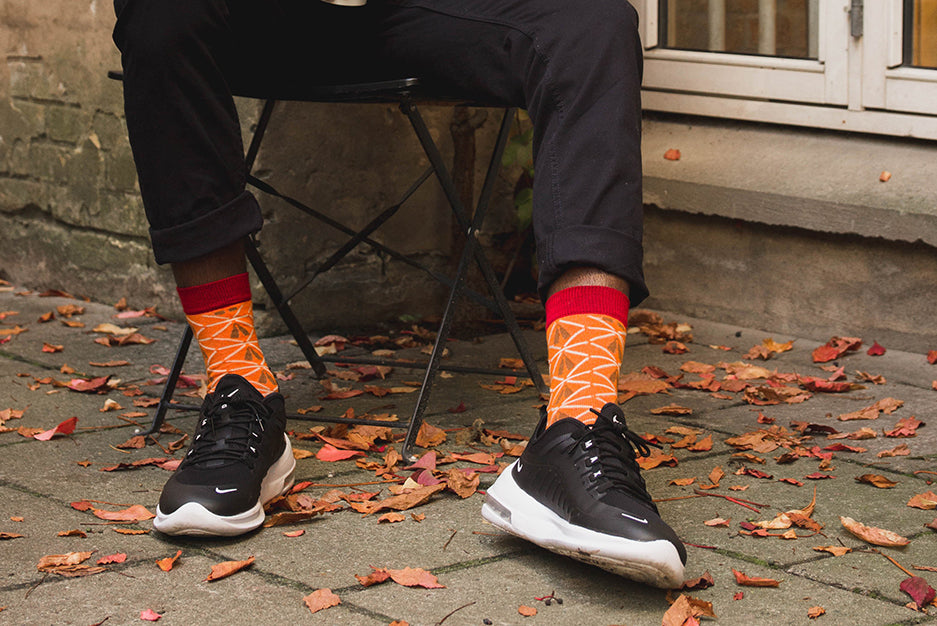 man sitting on a chair outside with red bamboo socks with african design