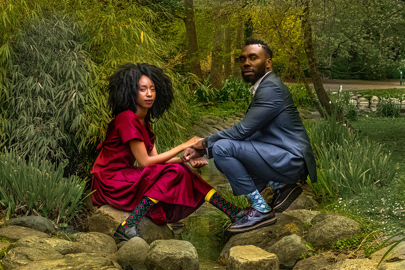 couple with black man and woman with suit, dress, colorful african bamboo dress socks sitting by water