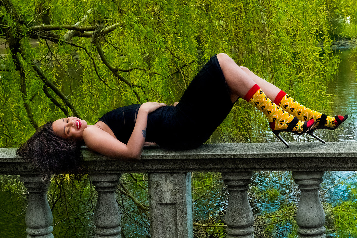 black woman with colorful african dress socks and heels lying down by a lake