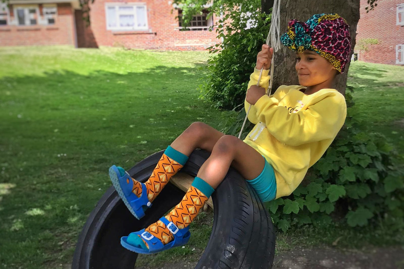 black girl on a swing with colorful african bamboo socks