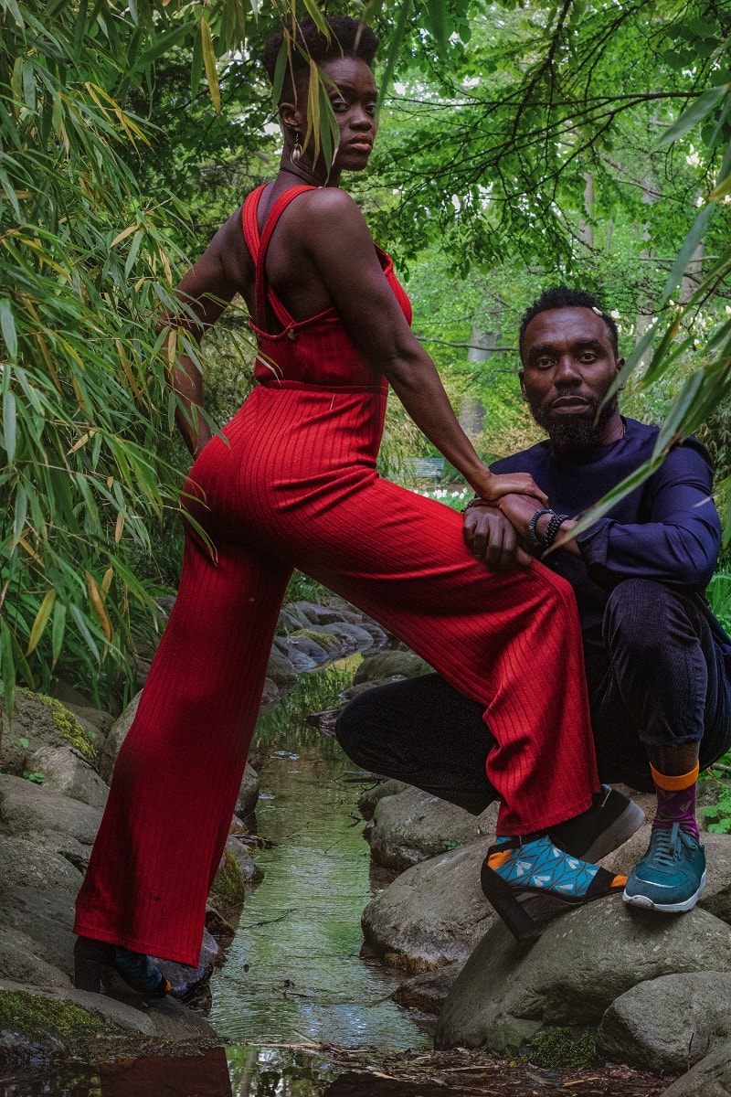 black man, black woman in red jumpsuit with african bamboo dress socks sneakers heels in nature