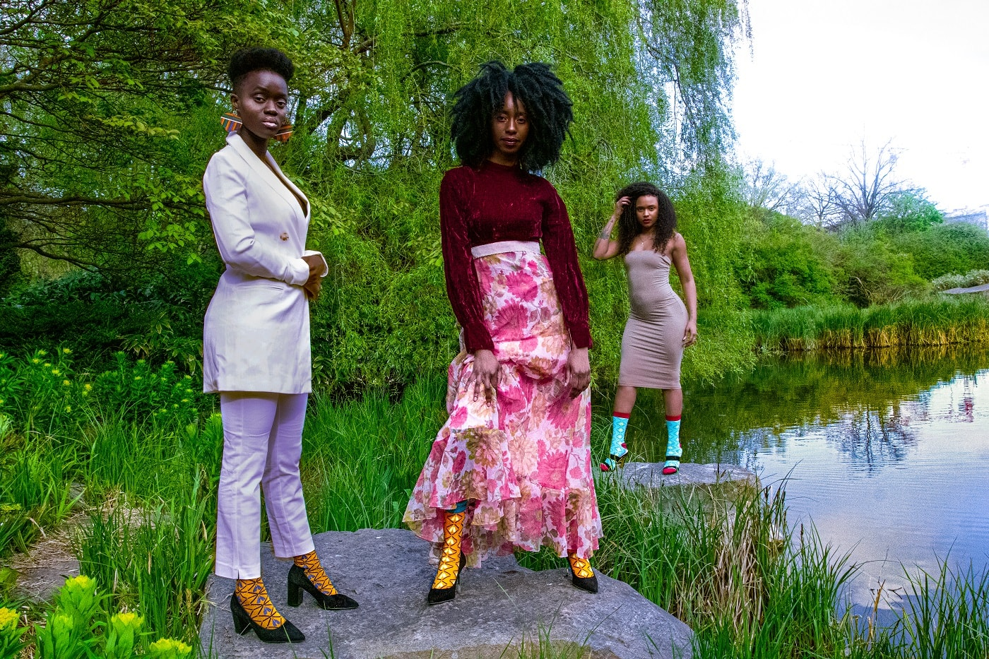 Three black women in colorful dresses and african bamboo socks standing by a lake