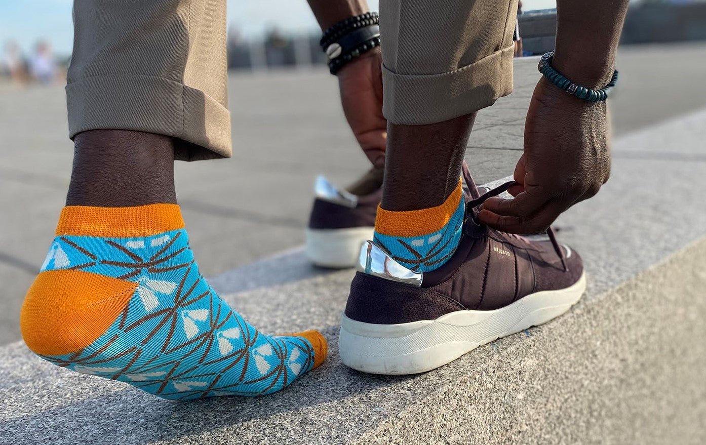 black man with beige pants, blue and orange ankle socks with african print