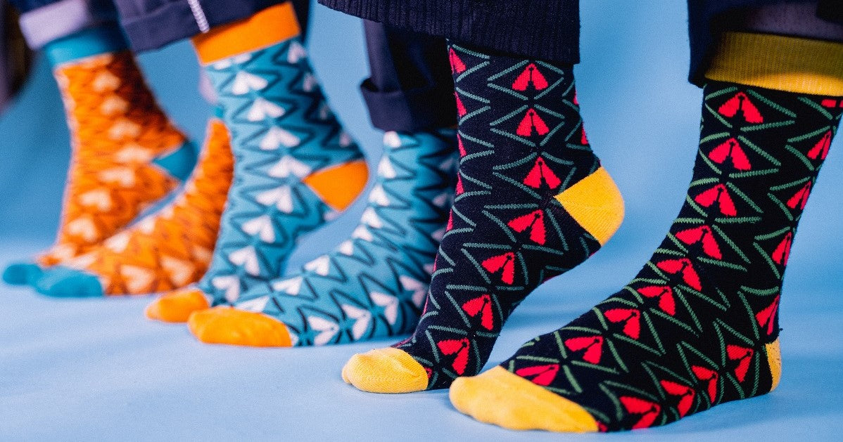 three pair of feet with black, blue, orange dress socks in bamboo with african print