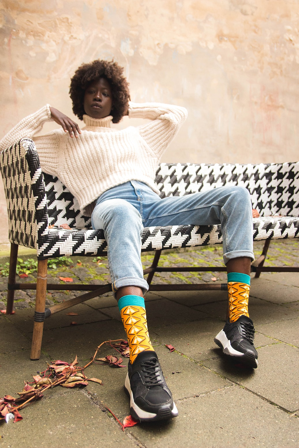african woman sitting on a bench outside with orange bamboo socks with african design
