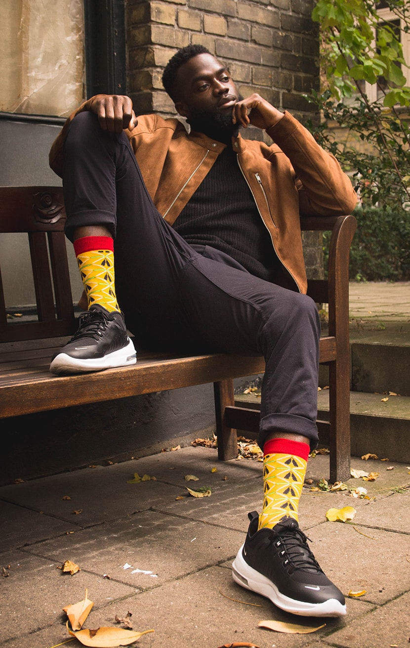 Black man sitting on a bench with yellow bamboo socks with african pattern