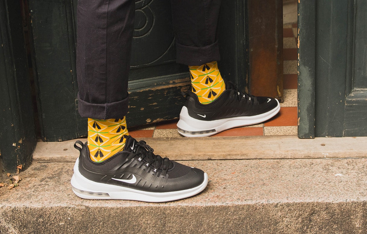 Two feet with yello bamboo socks with african design and black sneakers entering a door