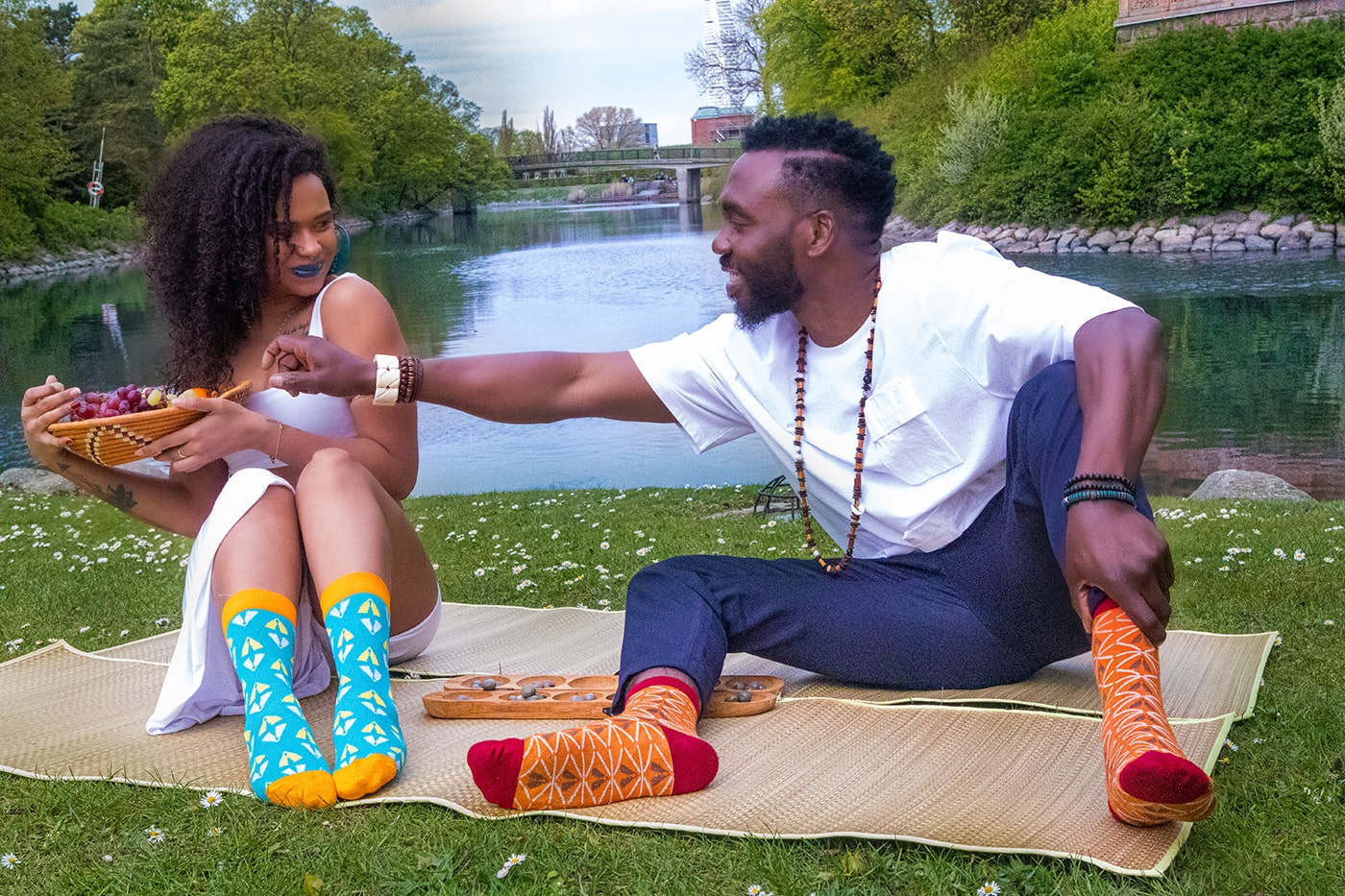 Black woman and man with colorful African bamboo socks eating fruits sitting by a river in Malmö