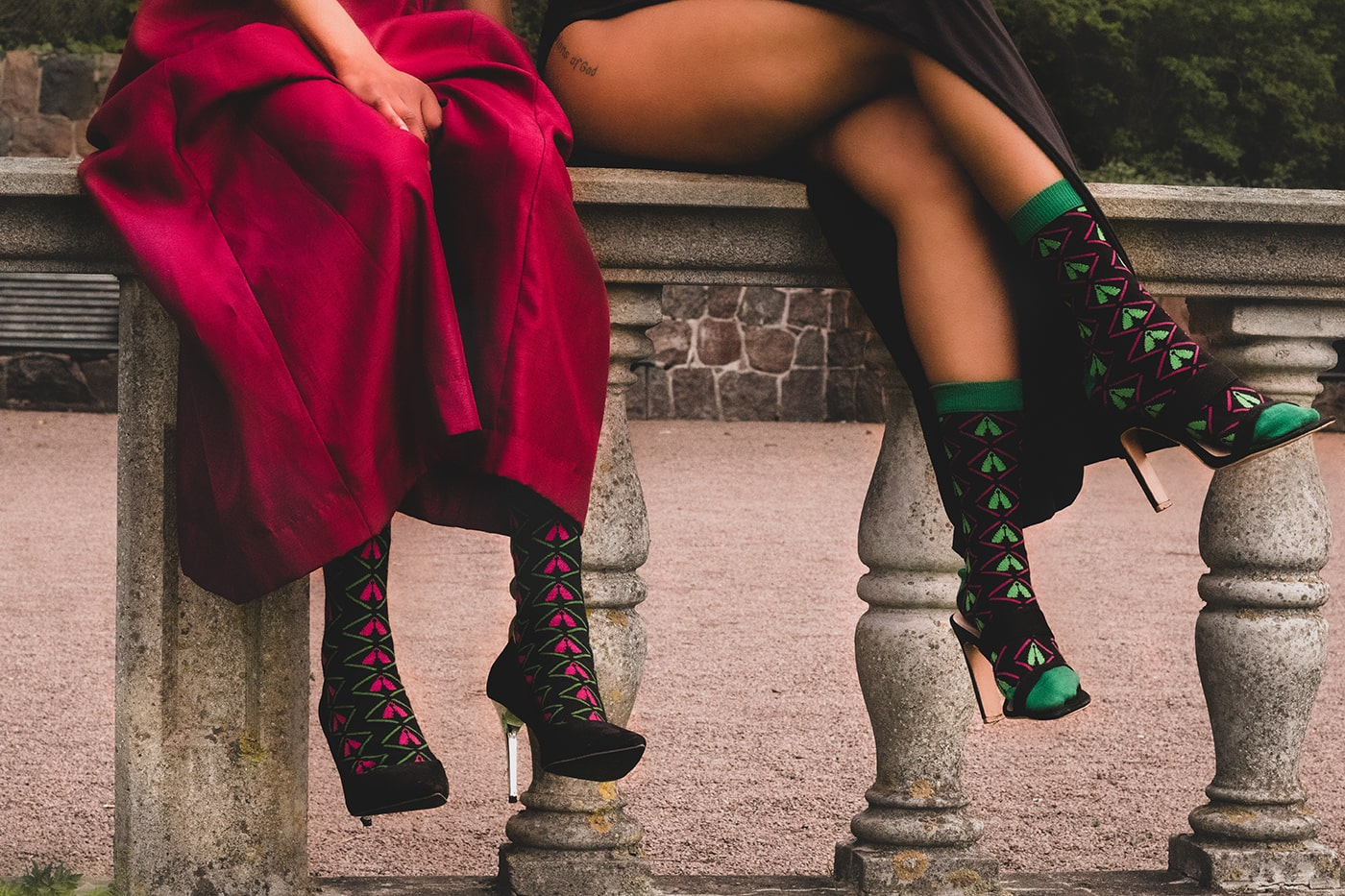 two women in dresses and black african bamboo dress socks in heels sitting on stone