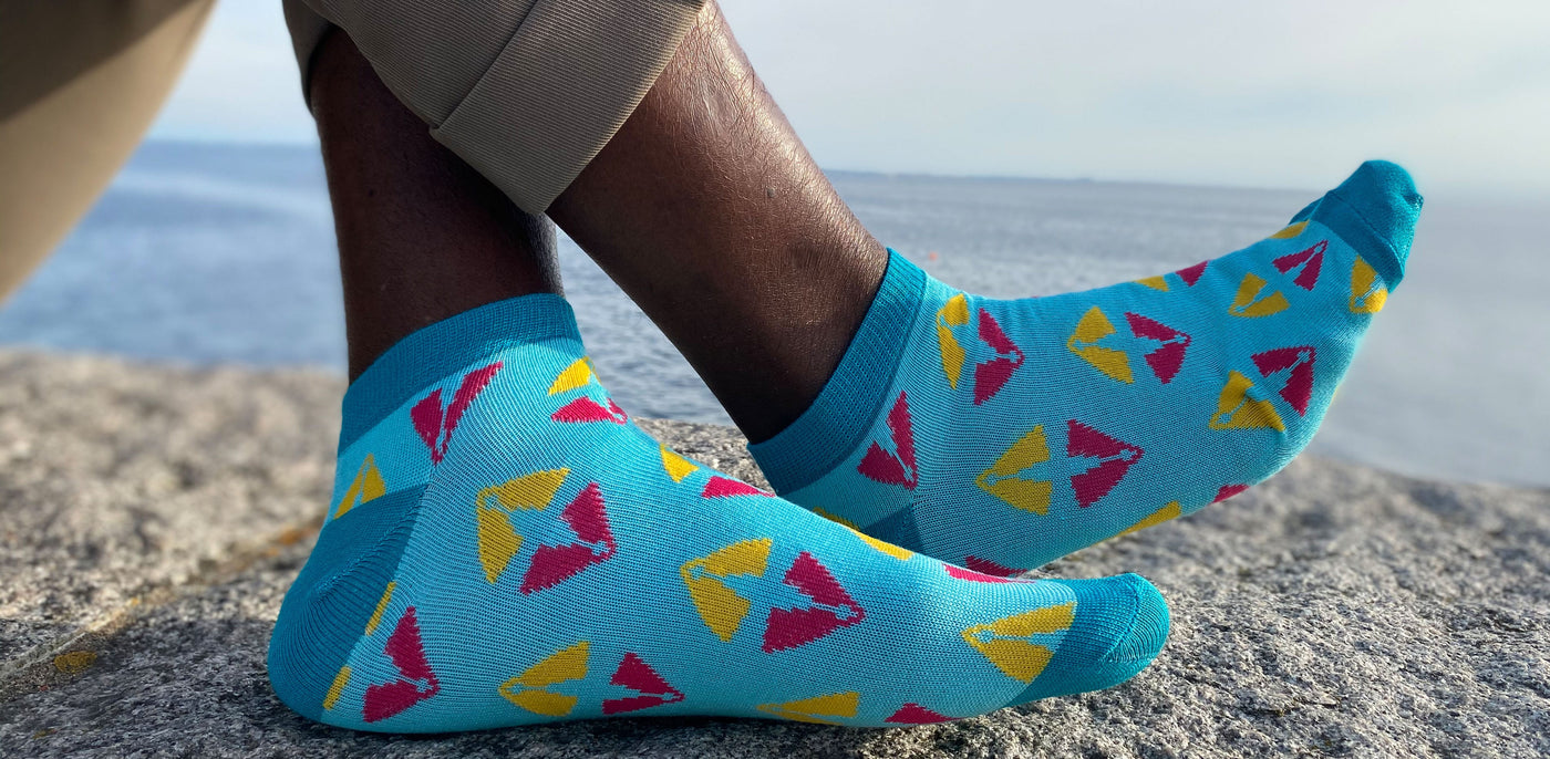 two feet with blue and pink colorful ankle socks in bamboo with african print