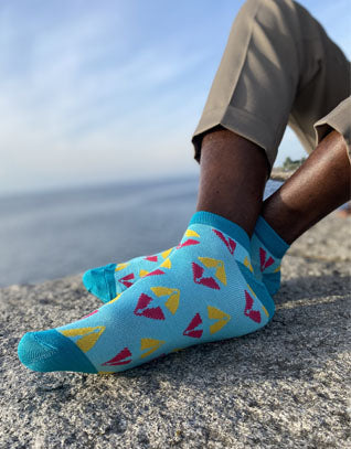 two feet with blue and pink ankle socks in bamboo with african print