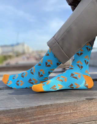 two feet with blue and orange colorful dress socks in bamboo with african print