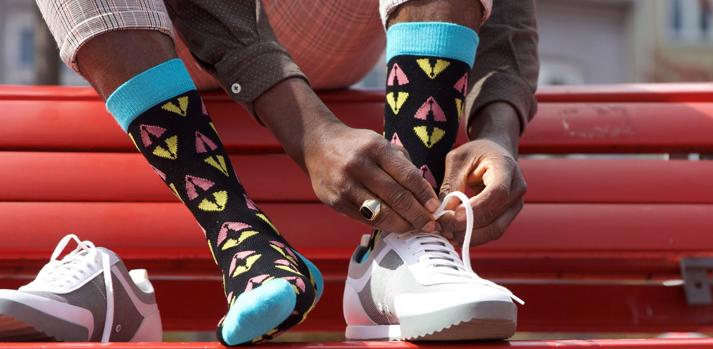 african man on a red bench with black dress socks in bamboo putting on white sneakers