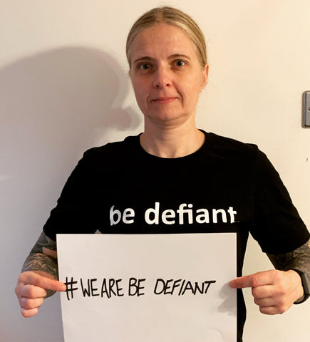 woman with tattooed arms in a black shirt holding a sign saying '#WeAreBeDefiant
