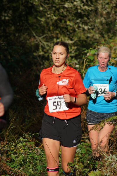 A woman trail running in black shorts and a red t shirt