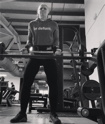 Black and white picture of a woman standing up doing bicep curls in the gym in a be defiant hoodie