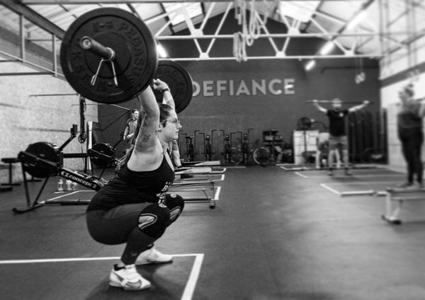 Woman Holding An Overhead Squat In Crossfit Workout