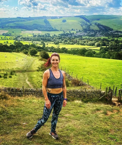 A Woman Wearing Leggings & A Sports Bra In Front Of Countryside Views