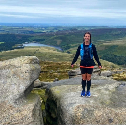 A Woman Standing On Top of A Rock In Front Of Hills Wearing Running Shoes And Long Socks
