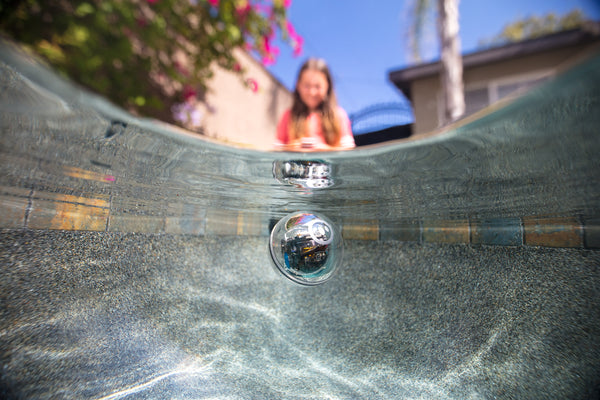 A young girl drives a Sphero BOLT through water in the backyard.