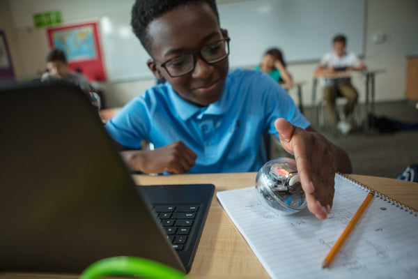 A boy sits at his desk in a classroom working on a computer with Sphero BOLT.