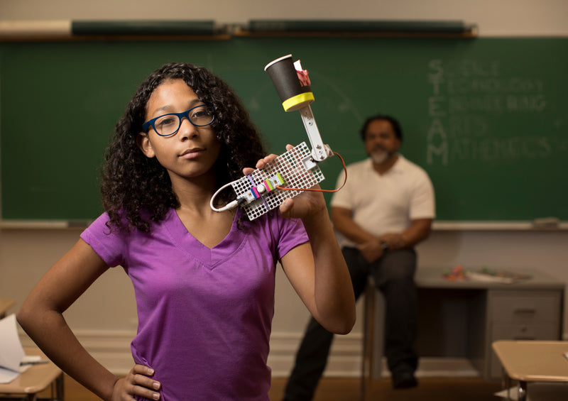 A teenage girl shows off her littleBits invention in her classroom while her teacher look on from the background.