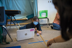 A girl in a mask lies on the floor of her classroom measuring distanced with a yard stick while programming her Sphero BOLT on a laptop.