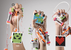 Three hands holding littleBits from the Code Kit.